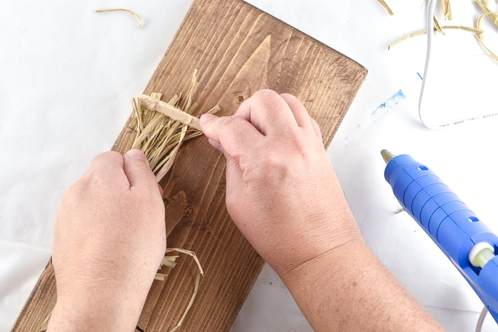 Glue down a little raffia so that it will look like it pops out of the burlap ribbon.