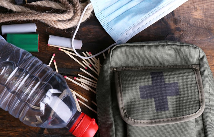 Emergency supplies like water, backpack, matches, rope and more laying on a table.